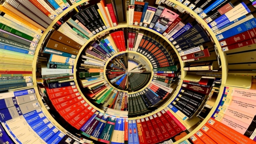 Altered photograph with fisheye top view of bookshelves full of books in concentric circles.