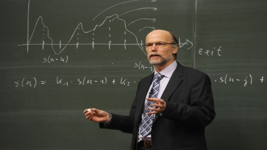 A photo of a professor holding chalk, standing in front of a chalkboard.