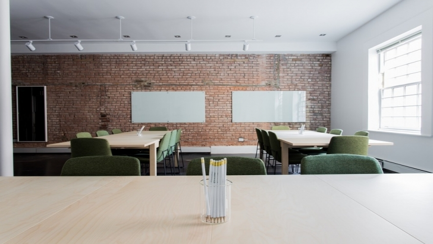 Photograph of a classroom with two tables surrounded by chairs and two whiteboards on a brick wall.