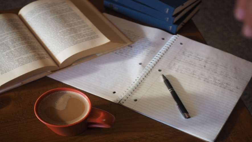 A photo of a tabletop with a stack of books, open notebook with handwritten notes and a pen, and a cup of coffee.