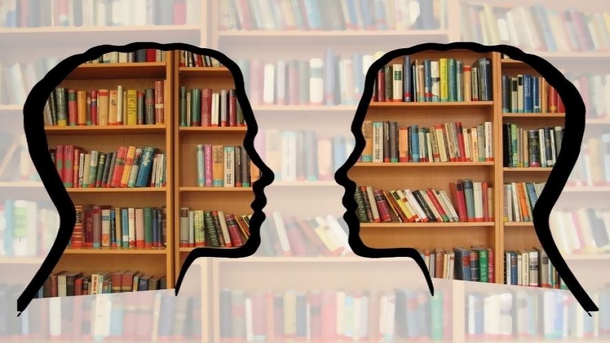 Image of two silhouetted heads in conversation, superimposed over a shelf of library books.