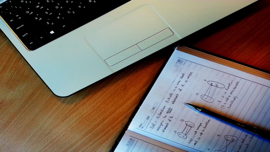 A photo of a laptop on a desk with an open notebook with mathematical functions written in it.