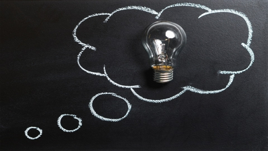 A photo of a blackboard with a chalk outline of a thought bubble and a lightbulb in the middle of the bubble.