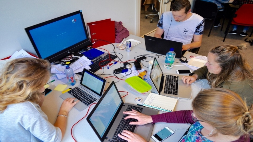 A photo of four people surrounding a table with several laptops, a desktop, papers, water bottles, cords, and cell phones.