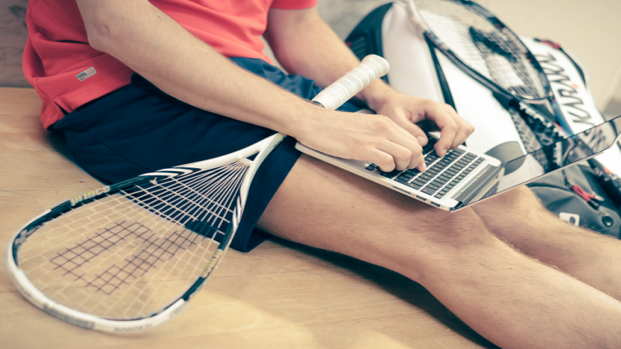 A photograph of a student, waist down, with a tennis racket laid across their lap, typing on a laptop computer in their lap.