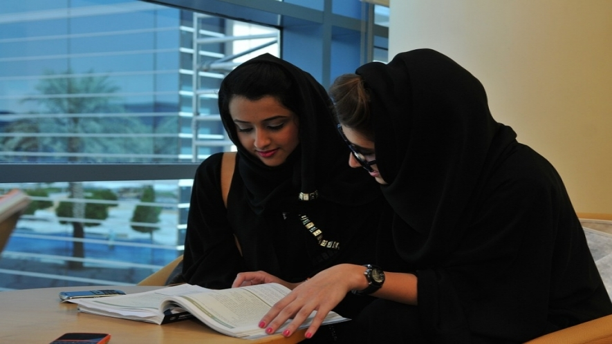 A photograph of two women sitting at a desk and looking over a textbook together.
