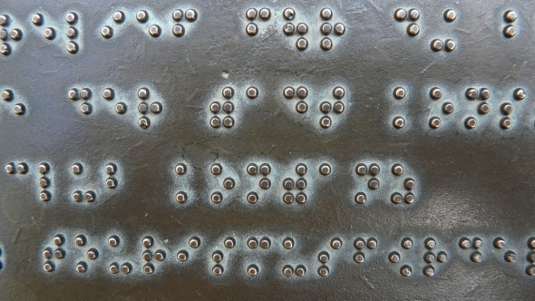 A photo of metal plate with braille on it.