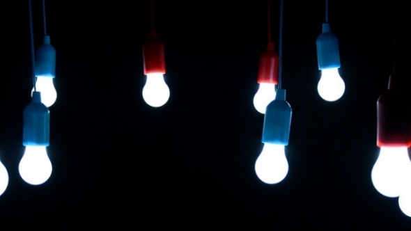 A photo of hanging light bulbs shining in the dark.
