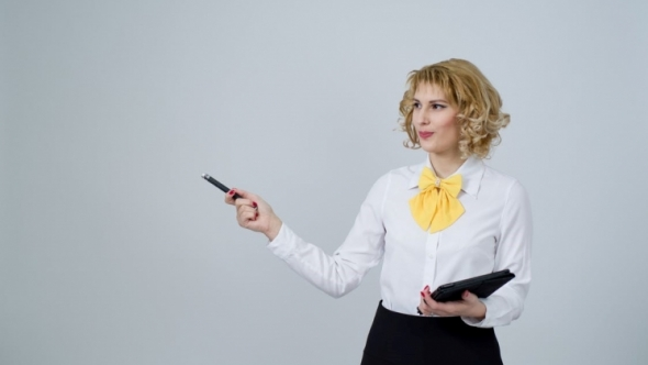 A photo of a blonde woman holding an electronic notebook and gesturing with a pen.