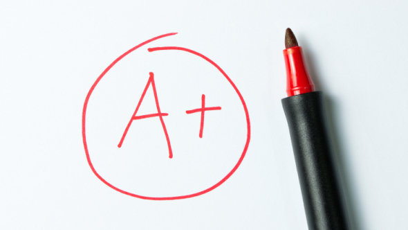 A photograph of a handwritten A plus grade in red marker with a red marker lying next to it.