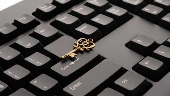 A photo of a keyboard with a skeleton key on it.