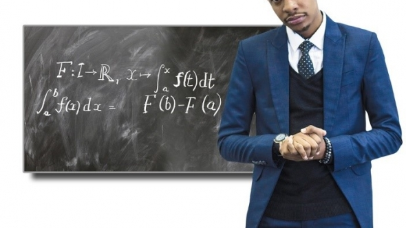 A photo of a male teacher standing in front of a chalkboard with calculus equations written on it.
