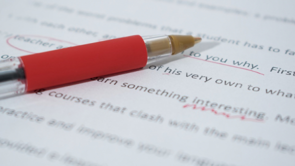 A photograph of a red pen on top of a typed paper with red markings.