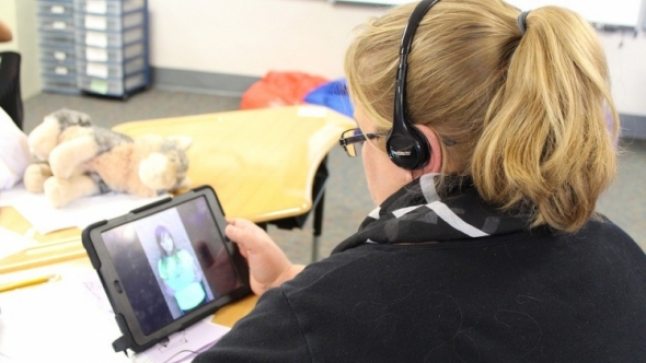 A photo of a person with headphones on, listening to a video of a person on their iPad.