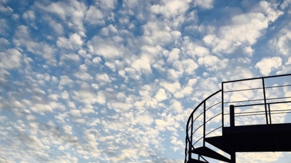 A photo of a staircase in the foreground with a cloudy sky in the background