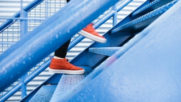 A photo of blue stairs with a person in red shoes running up them.