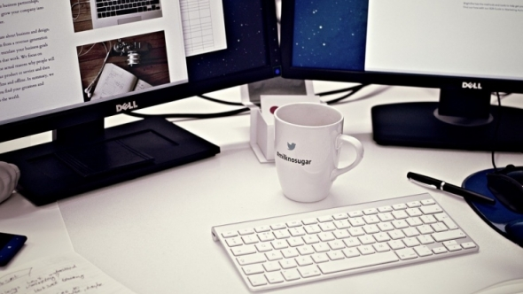 A photograph of a desk with two monitors, a keyboard, a coffee mug, and papers.