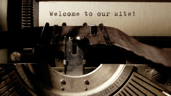 "A photo of a typewriter with the words ""Welcome to our site!"" typed on the paper in the machine."