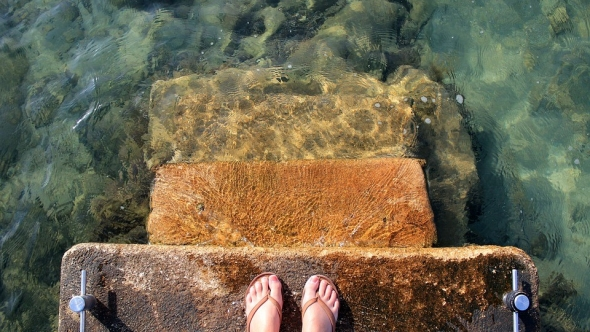 A photo of a person's feet standing on stone stairs leading into water.