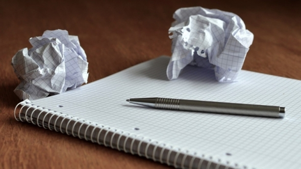 A photograph of a graph paper notebook with a pen and two crumbled up pieces of paper.