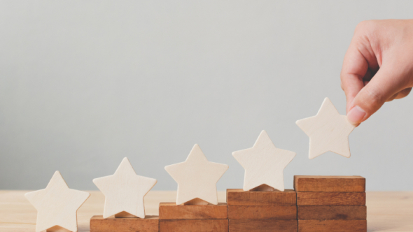 A photograph of wooden stars on top of elevated blocks with a hand placing the final star.