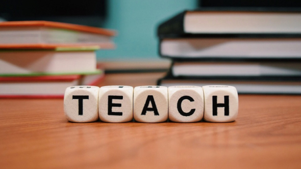 "A photograph of die on a desk spelling out the word ""Teach."""