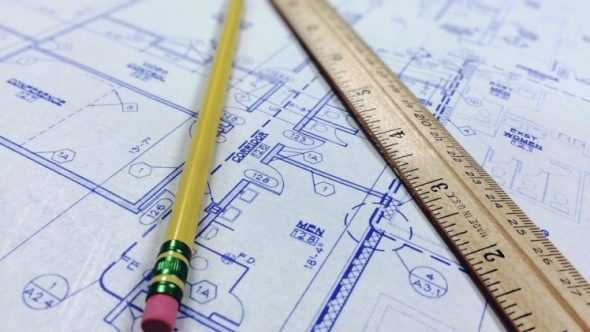 Close-up of a blueprint with a pencil and wooden ruler.